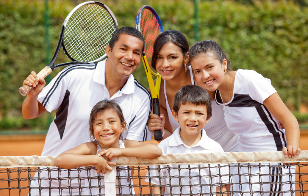 Happy family playing tennis.